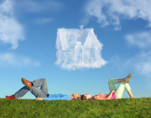Couple lying on grass looking at cloud of home